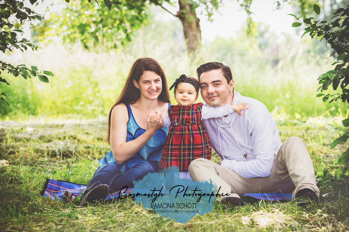 Familenfoto in der Natur auf einer Wiese. Mutter, Tochter, Vater sitzen auf einer Decke im Grünen